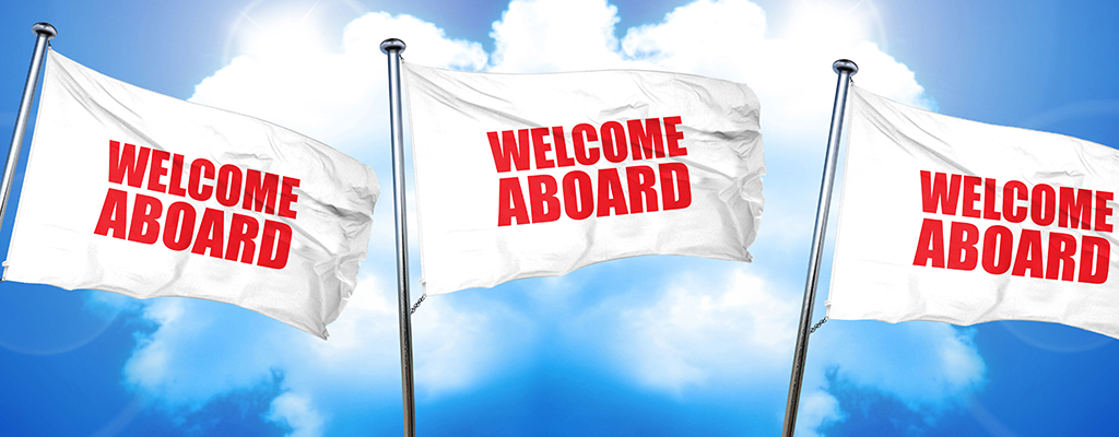 welcome aboard triple flags on a blue sky